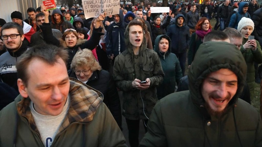"People shout slogans at a rally in Minsk, Belarus, Wednesday, March 15, 2017. Wednesday's march in the capital Minsk and smaller rallies at several other Belarusian cities were the latest in a series of demonstrations against the law that obliges citizens to pay the equivalent of $250 if they work less than half the year and do not register with state labor exchanges. Banner in the background reads ""Police, go over to the side of the people. The people will not offend you."" (AP Photo/Sergei Grits)"