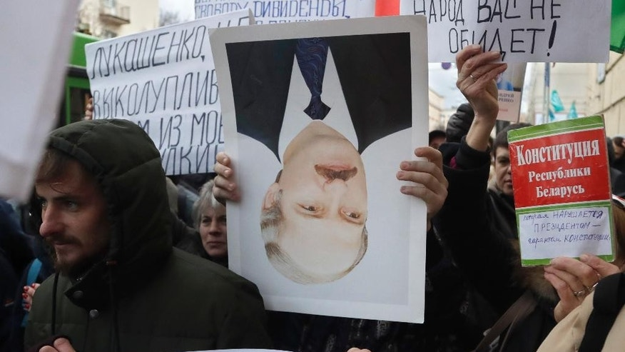 A protestor holds overturned portrait of Belarusian President Alexander Lukashenko during a rally in Minsk, Belarus, Wednesday, March 15, 2017. Wednesday's march in the capital Minsk and smaller rallies at several other Belarusian cities were the latest in a series of demonstrations against the law that obliges citizens to pay the equivalent of $250 if they work less than half the year and do not register with state labor exchanges. (AP Photo/Sergei Grits)