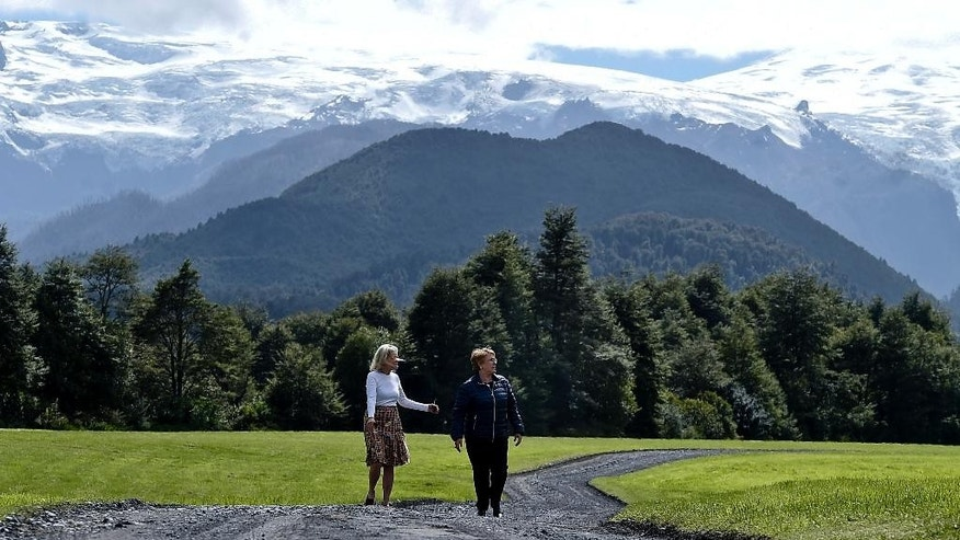 In this photo provided Chile's presidential office, Chile's President Michelle Bachelet, right, walks with Kristine McDivitt Tompkins, left, widow of late American conservationist Doug Tompkins in a natural reserve in Chaiten, Chile, Wednesday, March 15, 2017. The president received 407 thousand hectares donation from the Pumalín Foundation, as a donation from Tompkins widow Kris Mc Divitt. (Ximena Navarro/ Presidencia de Chile via AP)