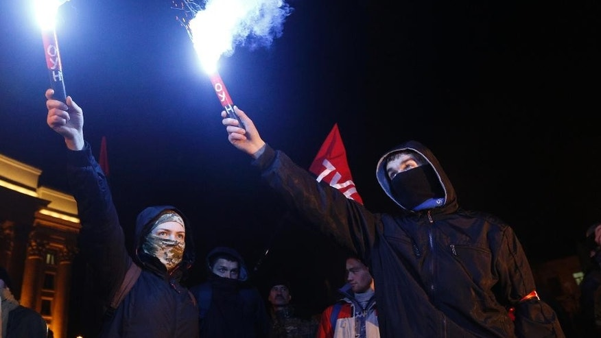 Far-right activists light flares during a protest in central Kiev, Ukraine, Tuesday, March 14, 2017. Activists and supporters of Ukrainian nationalist groups are demanding the closure of all banks associated with Russia in Ukraine. (AP Photo/Sergei Chuzavkov)