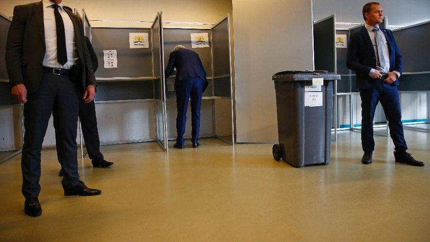Security guards look on as firebrand anti-Islam lawmaker Geert Wilders, center, prepares to cast his vote for the Dutch general election in The Hague, Netherlands, Wednesday, March 15, 2017. (AP Photo/Peter Dejong)