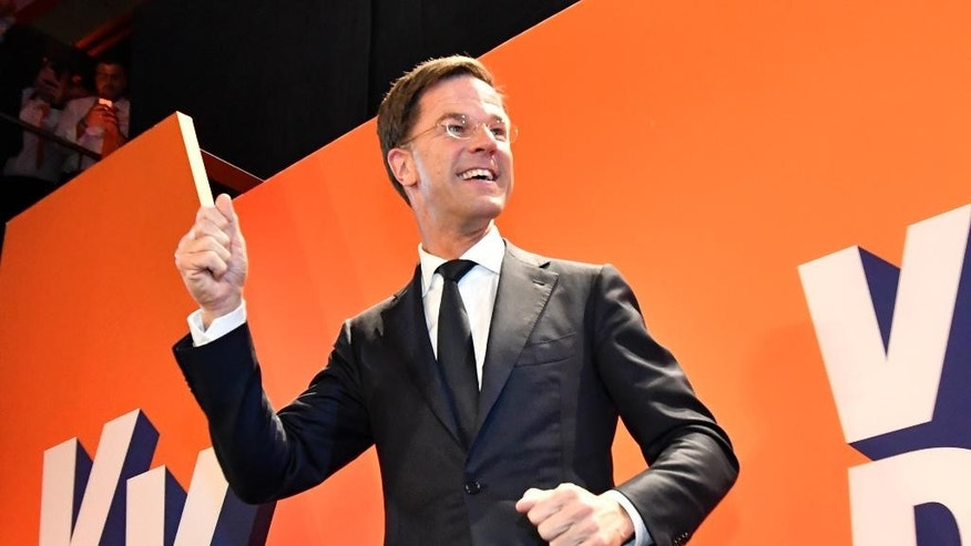 Prime Minister Mark Rutte of the free-market VVD party celebrates after exit poll results of the parliamentary elections were announced in The Hague, Netherlands, Wednesday, March 15, 2017. (AP Photo/Patrick Post)