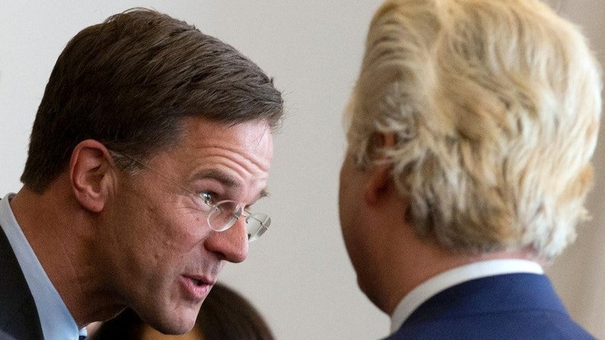 Dutch Prime Minister Mark Rutte, left, is greeted by right-wing populist leader Geert Wilders, right, during a meeting of party leaders with the chairwoman of the parliament to discus first steps in forming a new dutch coalition government in The Hague, Netherlands, Thursday, March 16, 2017. Dutch political parties were preparing Thursday to start what will likely be a long process of coalition talks after Prime Minister Mark Rutte's right-wing VVD easily won national elections, defying polls that suggested a close race with anti-Islam populist Geert Wilders. (AP Photo/Peter Dejong)