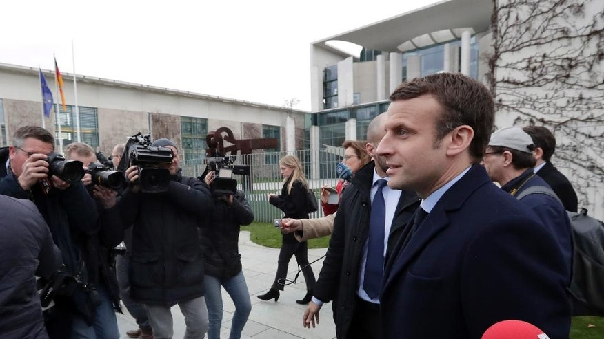Former French Economy Minister and candidate for the next presidential election Emmanuel Macron, right, is surrounded by media as he arrives for a statement in front of the chancellery after a meeting with German Chancellor Angela Merkel in Berlin, Germany, Thursday, March 16, 2017. (AP Photo/Michael Sohn)