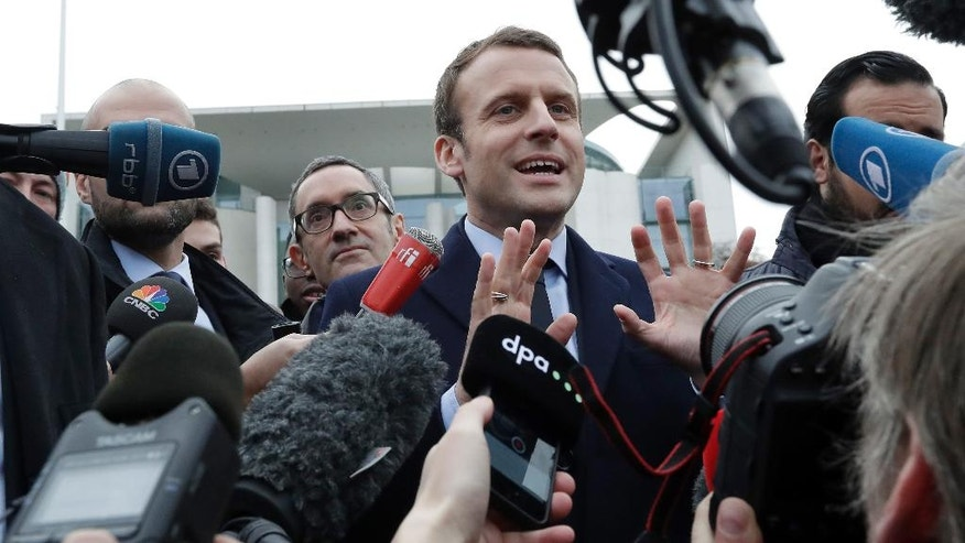 Former French Economy Minister and candidate for the next presidential election Emmanuel Macron, center, gestures as he arrives for a statement in front of the chancellery after a meeting with German Chancellor Angela Merkel in Berlin, Germany, Thursday, March 16, 2017. (AP Photo/Michael Sohn)