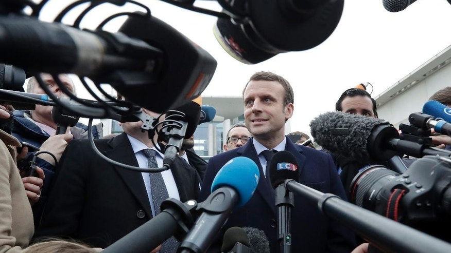 Former French Economy Minister and candidate for the next presidential election Emmanuel Macron, center, smiles as he arrives for a statement in front of the chancellery after a meeting with German Chancellor Angela Merkel in Berlin, Germany, Thursday, March 16, 2017. (AP Photo/Michael Sohn)