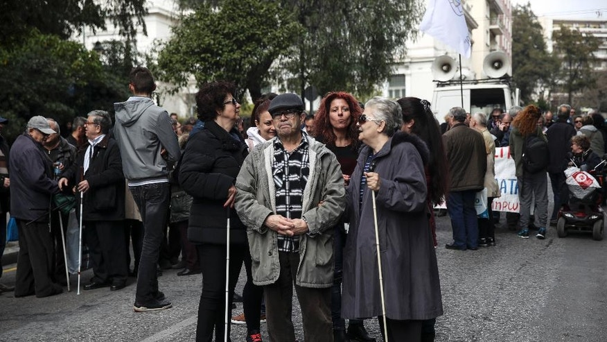 Visually impaired demonstrators march through the streets of the Greek capital during an anti-austerity rally in Athens, Thursday, March 16, 2017. Hundreds of people with disabilities took to the streets to protest against government's austerity measures which affect their income and state subventions. (AP Photo/Yorgos Karahalis)