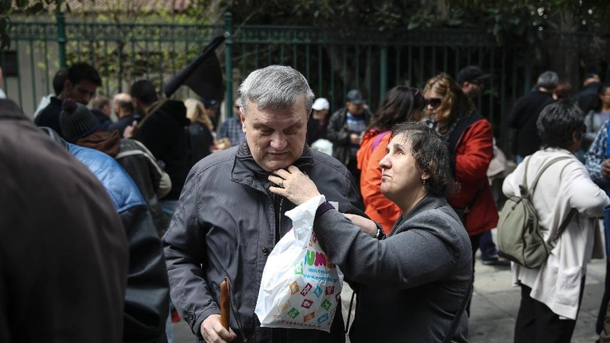 A visually impaired woman assists her husband to button up his coat during an anti-austerity rally in Athens, Thursday, March 16, 2017. Hundreds of people with disabilities took to the streets to protest against government's austerity measures which affect their income and state subventions. (AP Photo/Yorgos Karahalis)