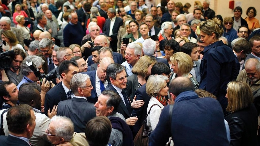 French conservative presidential candidate Francois Fillon, center, is surrounded by his supporters after delivering a speech during a campaign rally in Pertuis, southern France, Wednesday, March 15, 2017. Fillon is facing preliminary charges in an investigation of taxpayer-funded jobs his wife and children received but allegedly never performed. (AP Photo/Laurent Cipriani)