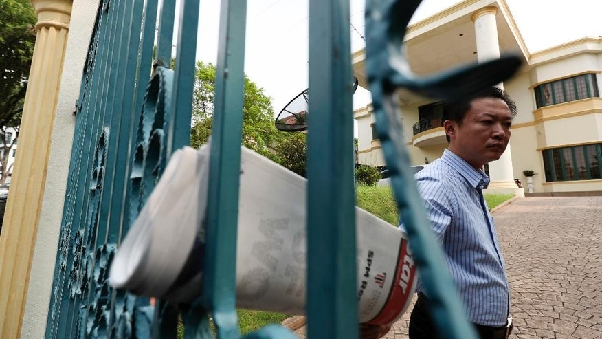 A staff member of the North Korean Embassy picks up a newspaper from the gate of the embassy in Kuala Lumpur, Malaysia, Thursday, March 16, 2017. A senior Malaysian police official said Thursday that the family of Kim Jong Nam, who was killed last month, has given consent to Malaysia to decide what to do with his body. (AP Photo/Vincent Thian)