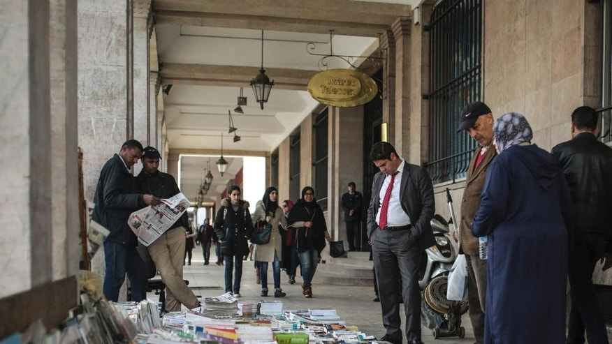 People look at newspapers and books at a stall near the Medina of Rabat, Morocco, Thursday, March 16, 2017. In a highly unusual move, Morocco's king has ousted the designated prime minister in an effort to settle a five-month deadlock over forming a new government. (AP Photo/Mosa'ab Elshamy)