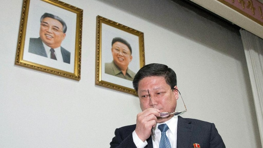 CORRECTS NAME SPELLING - Pak Myong Ho, minister of the North Korean Embassy in China, walks past portraits of the late North Korean leaders Kim Il Sung, left, and Kim Jong Il during a press conference in Beijing, China, Thursday, March 16, 2017. Pak says Pyongyang must act in self-defense against the U.S. and South Korea's joint military drills, which he said have brought the region to the brink of nuclear war. (AP Photo/Ng Han Guan)