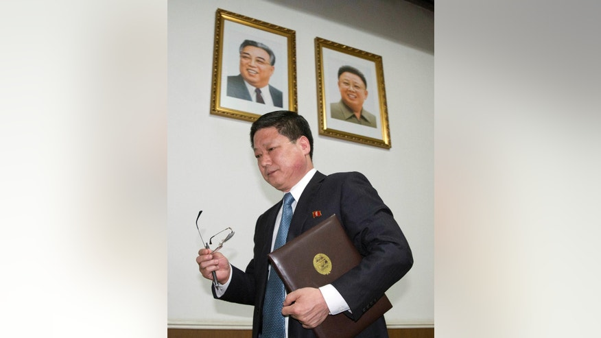 Pak Myong Ho, minister of the North Korean Embassy in China, walks past portraits of the late North Korean leaders Kim Il Sung, left, and Kim Jong Il during a press conference in Beijing, China, Thursday, March 16, 2017. Pak says Pyongyang must act in self-defense against the U.S. and South Korea's joint military drills, which he said have brought the region to the brink of nuclear war. (AP Photo/Ng Han Guan)