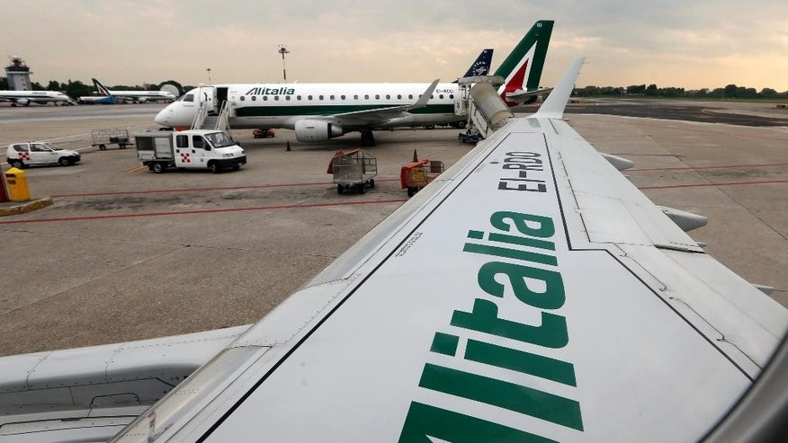 In this picture taken  Wednesday, May 7, 2014, Alitalia planes are parked on the tarmac prior to take off from the Linate airport, in Milan, Italy. Unions representing Alitalia workers on Friday, March 17, 2017, announced a strike on April 5 to protest deep job and salary cuts as part of a new plan to relaunch the struggling airline. (AP Photo/Luca Bruno)