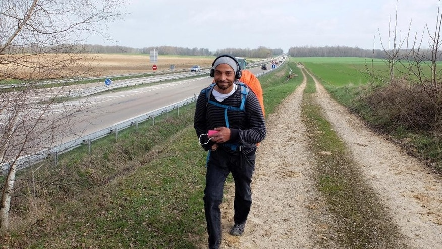 Abdelghani Merah walks near Sezanne, 100 km (62 miles) east of Paris, Friday, March 17, 2017. Five years after his brother Mohamed Merah killed seven people in the name of Islam, Abdelghani Merah is now walking across France to preach tolerance and warn against the dangers of religious radicalism. (AP Photo/Nicolas Garriga)