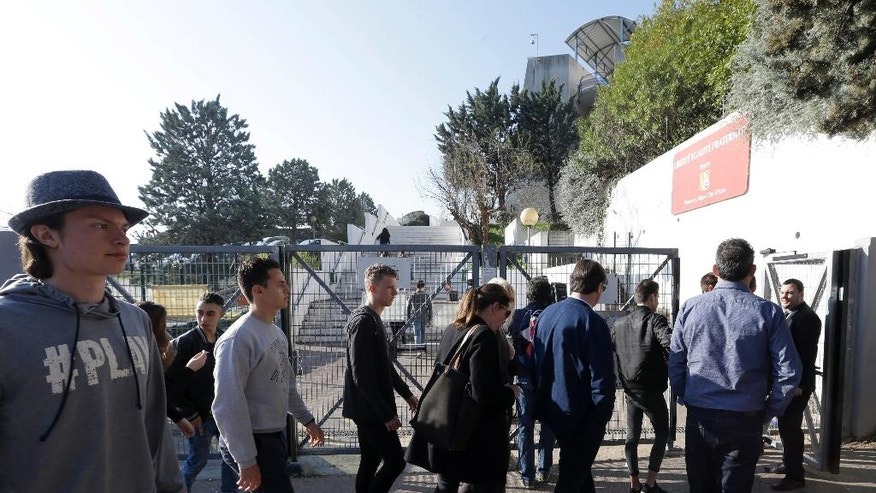 High school students enter the Alexis de Tocqueville school in Grasse, southern France, the day after a 16-year-old student opened fire, wounding three other students and the principal, Friday, March 17, 2017. A 16-year-old student who had troubled relations with his peers opened fire at a high school in southern France on Thursday, wounding three other students and the principal who tried to intervene, officials said. (AP Photo/Claude Paris)