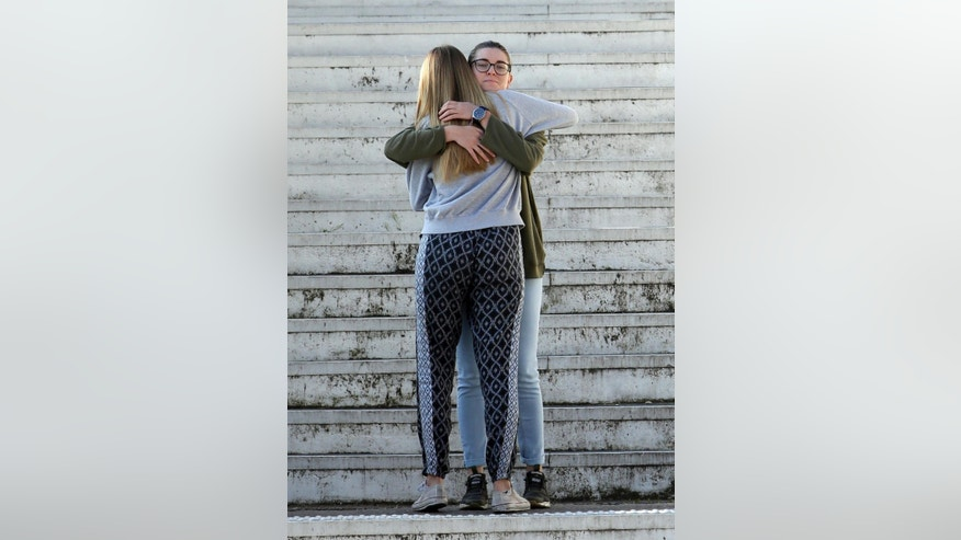 Two High school students hug each other as they climb the steps leading to the Alexis de Tocqueville school in Grasse, southern France, the day after a 16-year-old student opened fire, wounding three other students and the principal, Friday, March 17, 2017. A 16-year-old student who had troubled relations with his peers opened fire at a high school in southern France on Thursday, wounding three other students and the principal who tried to intervene, officials said. (AP Photo/Claude Paris)