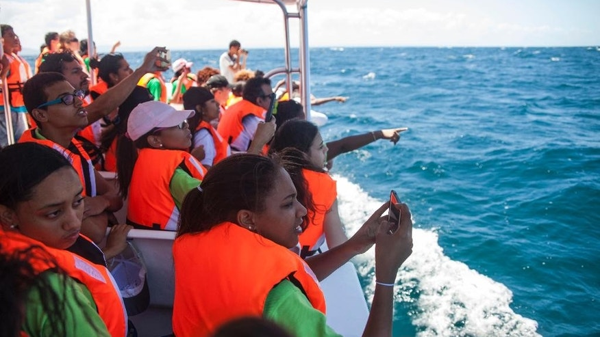 In this Tuesday, March 14, 2017 photo, students from the St. Rose Institute for Deaf Assistance spot whales during a tour off Samana, Dominican Republic. Dozens of them wore high-tech backpacks that turn whale songs into vibrations. Introducing deaf and hearing-impaired students to the whales and their music was the vision of Dominican artist and musician Maria Batlle, who founded the Muse Seek Project. (AP Photo/Tatiana Fernandez)
