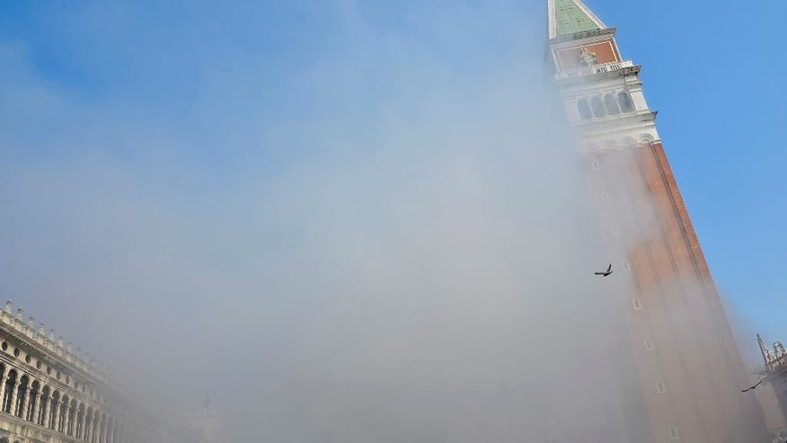 Smoke rises in famous St. Mark Square in Venice, Italy, Friday, March 17, 2017. News reports say thieves attempting to rob a jewelry store in Venice's St. Mark's Square set off panic among tourists when they ignited smoke bombs to cover their movements. (Andrea Venturini via AP )
