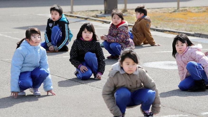 Elementary school students crouch during an evacuation drill in Oga, Aomori prefecture, northern Japan Friday.