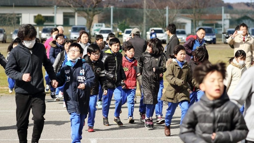 Elementary school students and others take shelter during an evacuation drill in Oga, Aomori prefecture, northern Japan Friday.