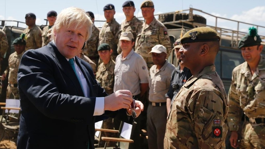 Britain's Foreign Secretary Boris Johnson, left, awards a Long Service and Good Conduct (LSGC) medal to Mohamed Shan at the British Army Training Unit Kenya (BATUK), in Ole Naishu near Nanyuki, in Kenya Friday, March 17, 2017. Johnson is later expected to hold bilateral talks in the capital Nairobi. (Thomas Mukoya/Pool via AP)