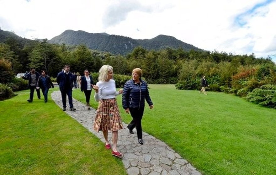 Chile's President Michelle Bachelet, right, walks with Kristine McDivitt Tompkins,left, widow of late American conservationist Doug Tompkins in a natural reserve in Chaiten, Chile, Wednesday, March 15, 2017. The president received 407 thousand hectares from the Pumalín Foundation, as a donation from Tompkins widow Kris Mc Divitt. (Ximena Navarro/ Presidencia de Chile via AP)