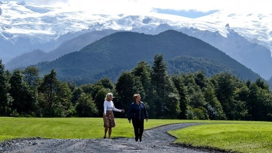 Chile's President Michelle Bachelet walks with Kristine McDivitt Tompkins in a natural reserve in Chaiten, Chile, on March 15, 2017