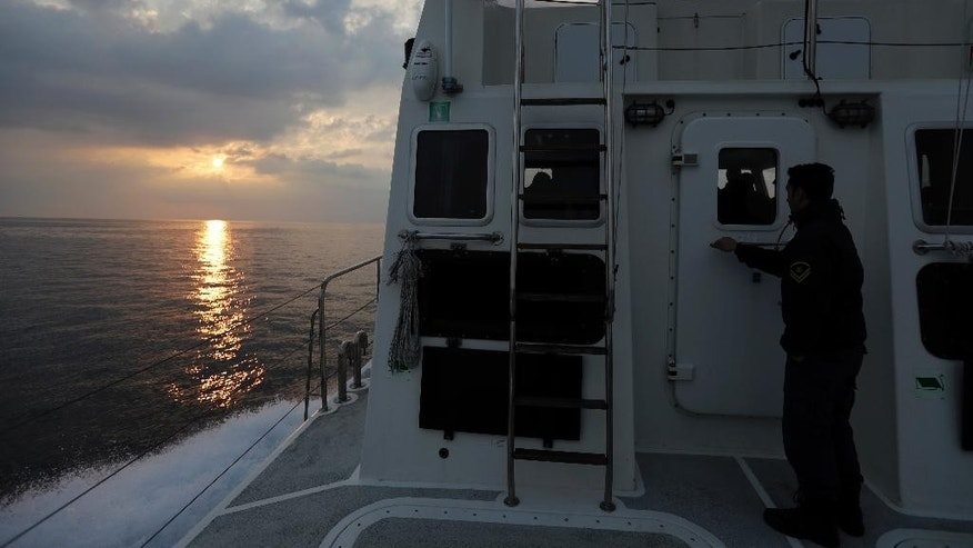 In this photo taken on Friday, March 17, 2017 the sun rises as a Greek coast guard vessel patrols on the Aegean Sea near the northeastern Greek island of Lesbos. The waters off northern Lesbos once resounded to the shrieks of the drowning, the whine of outboard motors as refugees struggled to reach Europe alive, and the thudding of rescue helicopter engines. A million people crossed the straits between Turkey and Greece's eastern Aegean islands in the year before March 20, 2016, and hundreds drowned. About half of those who made it landed on this island. (AP Photo/Thanassis Stavrakis)