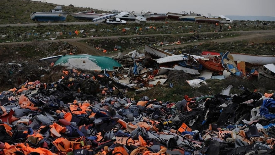 In this photo taken on Thursday, March 16, 2017 boats and piles of life jackets used by refugees and migrants lie at a dump in Molyvos village, on the northeastern Greek island of Lesbos. The waters off northern Lesbos once resounded to the shrieks of the drowning, the whine of outboard motors as refugees struggled to reach Europe alive, and the thudding of rescue helicopter engines. A million people crossed the straits between Turkey and Greece's eastern Aegean islands in the year before March 20, 2016, and hundreds drowned. About half of those who made it landed on this island. (AP Photo/Thanassis Stavrakis)