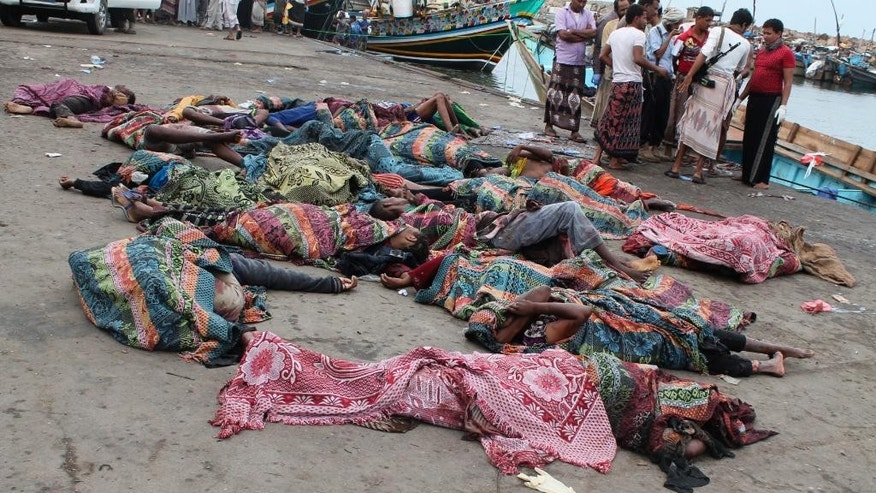 Bodies of Somali migrants, killed in attack by a helicopter while traveling in a boat off the coast of Yemen, lie on the ground at Hodeida city, Yemen, Friday, Mar. 17, 2017. A helicopter gunship attacked a boat packed with Somali migrants off the coast of Yemen overnight Thursday, killing at least 31 people, according to a U.N. agency, Yemeni officials and a survivor who witnessed the attack. (AP Photo/Abdel-Karim Muhammed)
