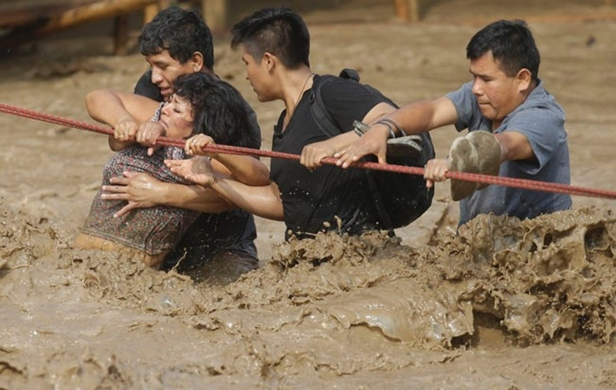 A group of people, stranded in flood waters, hold onto a rope as they wade through flood waters to safety in Lima, Peru, Friday, March 17, 2017. Intense rains and mudslides over the past three days have wrought havoc around the Andean nation and caught residents in Lima, a desert city of 10 million where it almost never rains, by surprise. (AP Photo/Martin Mejia)