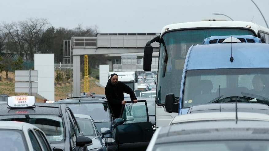 A man watches the traffic on the highway leading to the Orly airport, south of Paris, Saturday, March, 18, 2017. A man was shot to death Saturday after trying to seize the weapon of a soldier guarding Paris' Orly Airport, prompting a partial evacuation of the terminal, police said. (AP Photo/Thibault Camus)