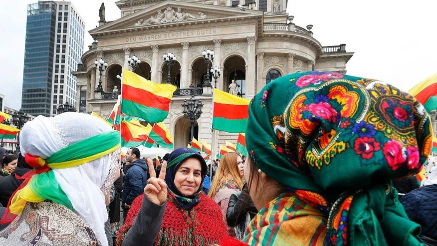 Kurdish women in traditional costumes living in Germany stand together on the square in front of the Old Opera in Frankfurt, Germany, Saturday, March 18, 2017. Thousands celebrate the Newroz spring festival and protest against Turkish President Erdogan. (AP Photo/Michael Probst)