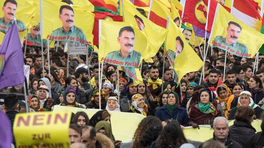Kurds living in Germany gather and wave flags with portraits of detained Kurdish PKK Leader Abdullah Ocalan in Frankfurt, Germany, Saturday, March 18, 2017. Thousands celebrate the Newroz spring festival and protest against Turkish President Erdogan. (Boris Roessler/dpa via AP)