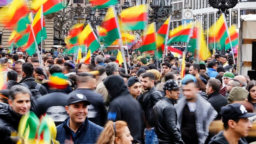 Kurds living in Germany gather and wave flags on the square in front of the Old Oprea in Frankfurt, Germany, Saturday, March 18, 2017. Thousands celebrate the Newroz spring festival and protest against Turkish President Erdogan. (AP Photo/Michael Probst)