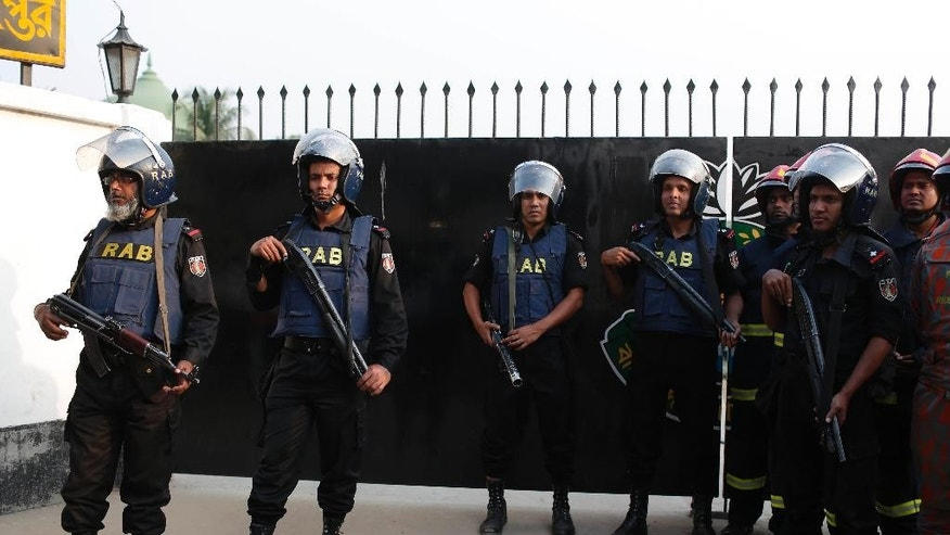 Members of the Rapid Action Battalion (RAB) stand guard at the entrance of their camp where an unidentified intruder has died in a blast, in Dhaka, Bangladesh, Friday, March 17, 2017. A suspected militant died Friday when he exploded a bomb at the future headquarters of the Bangladesh security agency, officials said. (AP Photo)