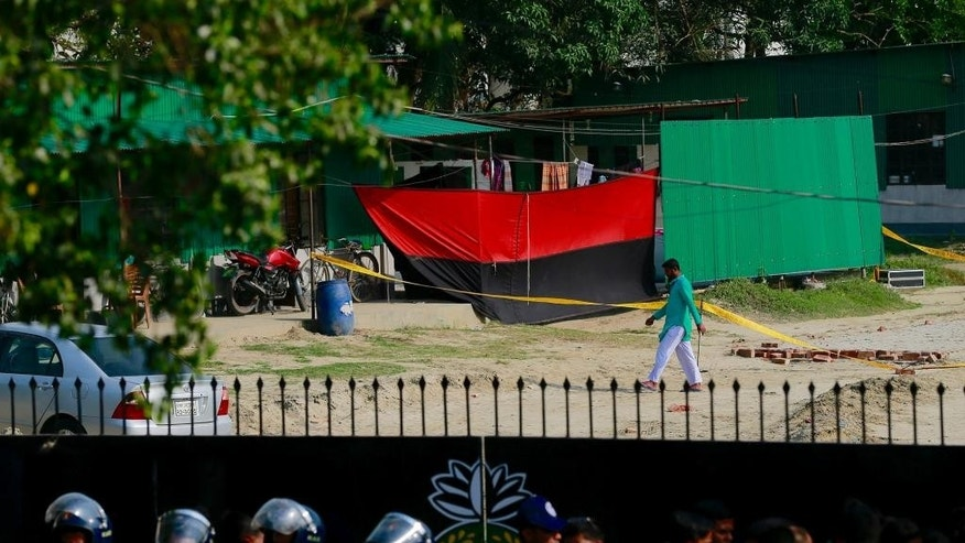 Members of the Rapid Action Battalion (RAB) stand guard at the entrance of a camp of the RAB as a man walks across the spot where an unidentified intruder has died in a blast in Dhaka, Bangladesh, Friday, March 17, 2017. A suspected militant died Friday when he exploded a bomb at the future headquarters of the Bangladesh security agency, officials said. (AP Photo)