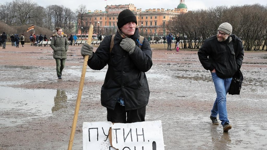 A man displays a poster reading 'Putin out!' during a protest rally against decision of the city authorities to hand over the city's landmark St. Isaac's Cathedral to the Russian Orthodox Church in St.Petersburg, Russia, Saturday, March 18, 2017. About four thousand people gathered for a protest against the controversial return of the renowned cathedral to the Russian Orthodox Church. (AP Photo/Dmitri Lovetsky)