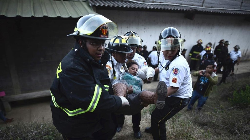 Firefighters carry a woman who fainted outside a reformatory for youth and men, Centro Correccional Etapa II, where a riot and fire broke out in San Jose Pinula, Guatemala, Sunday, March 19, 2017. At least one man died, a jail monitor, during the riot, according the police spokesman Pablo Castillo. (AP Photo/Oliver de Ros)
