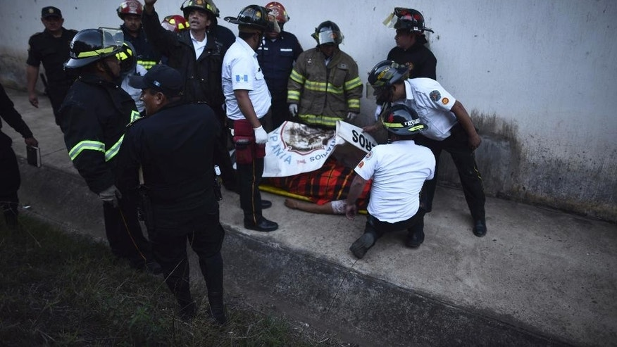 Firefighters surround a man's body inside a reformatory for youth and men during a riot at the Centro Correccional Etapa II in San Jose Pinula, Guatemala, Sunday, March 19, 2017. At least one man died, a jail monitor, during the riot, according the police spokesman Pablo Castillo. (AP Photo/Oliver de Ros)