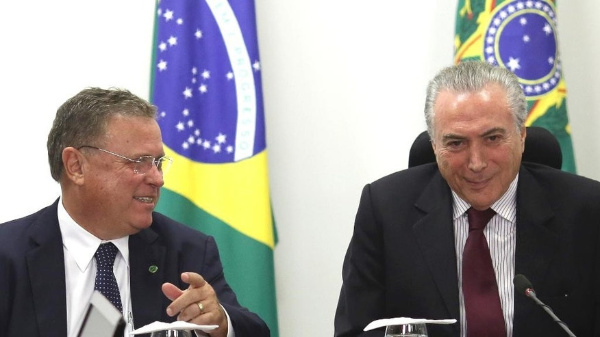 Brazil's President Michel Temer, right, sits with Agriculture Minister Blairo Maggi during a meeting on the rotten meat scandal with representatives of the agriculture and meat sector at Planalto presidential palace in Brasilia, Brazil, Sunday, March 19, 2017. Temer is holding several meetings on Sunday in light of a recent corruption probe that revealed Brazilian meatpackers bribed inspectors to keep rotten meat on the market. (AP Photo/Eraldo Peres)