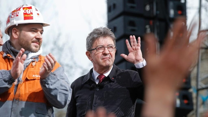 Far-left presidential candidate Jean-Luc Melenchon acknowledges applauses as he walks on stage during a gathering in Paris, Saturday, March 18, 2017. Far-left French presidential candidate Jean-Luc Melenchon gathered tens of thousands of supporters in Paris at a rally Saturday calling for deep reforms in the French constitution. (AP Photo/Michel Euler)