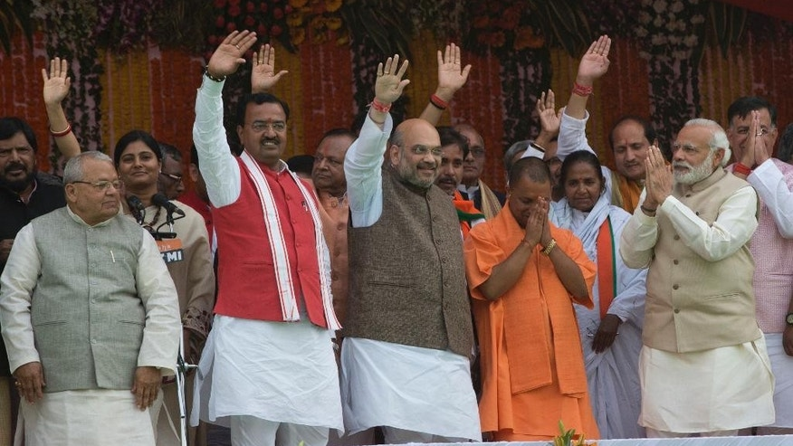 Indian Prime Minister Narendra Modi, second right and Yogi Adityanath, in saffron robes, greet with folded hands as Bharatiya Janata Party president Amit Shah, center and others wave to the audience after Adityanath was sworn in as Uttar Pradesh state chief minister in Lucknow, India, Sunday, March 19, 2017.  (AP Photo/Rajesh Kumar Singh)