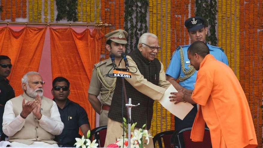Indian Prime Minister Narendra Modi, left, watches as Yogi Adityanath, standing right greets Governor Ram Naik, after taking oath as Uttar Pradesh state chief minister in Lucknow, India, Sunday, March 19, 2017. (AP Photo/Rajesh Kumar Singh)