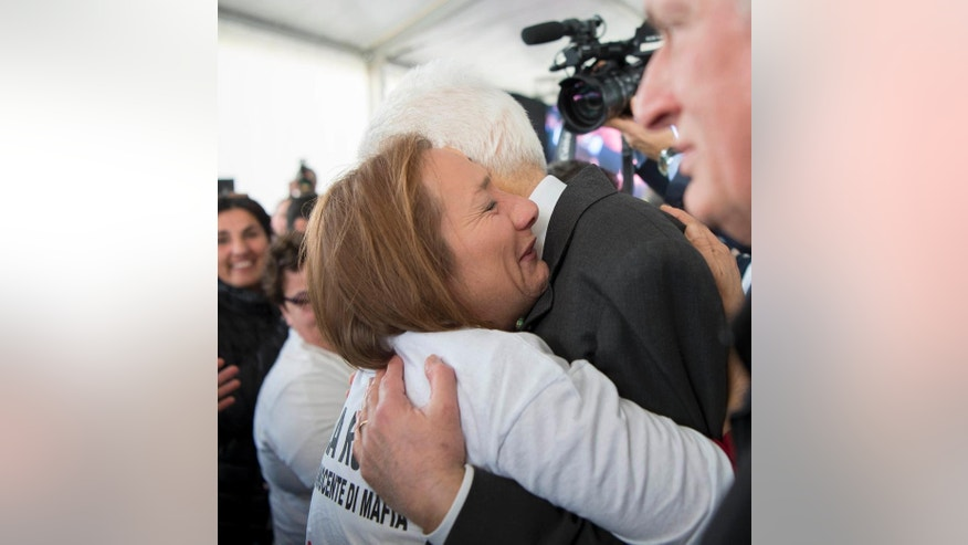 Italian Presdient Sergio Mattarella, right, hugs an unidentified woman at an event to honor victims of Mafia crimes, in the Calabrian town of Locri, southern Italy, Sunday, March 19, 2017. Mattarella on Sunday paid tribute to those slain for opposing organized crime, including judges, police officers, union leaders, entrepreneurs, and politicians, like his own brother, who were killed by the mob. (Francesco Ammendola/Italian Presidential Press Service pool photo via AP)
