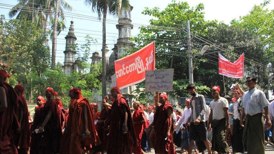 Hard-line Buddhists including monks walk by a mosque during a protest march, led by Rakhine State's dominant Arakan National Party, against the government's plan to give citizenship to some members of the persecuted Rohingya Muslim minority community in Sittwe, Rakhine state, Myanmar, Sunday, March 19, 2017. Many Rohingya lived in Sittwe, the state capital, before an outbreak of inter-communal violence in 2012 forced them to flee their homes. (AP Photo/Esther Htusan)