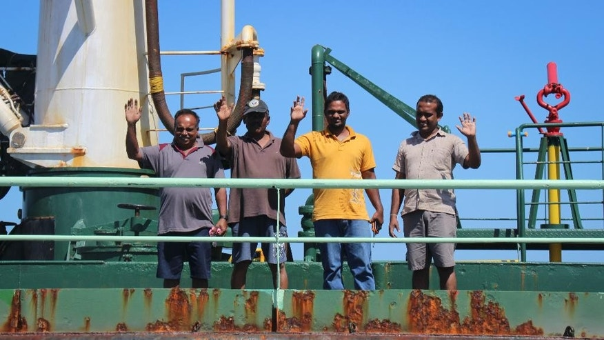 Crew members wave from aboard the Aris 13 oil tanker, which was released by pirates after negotiations by officials and local elders, during a visit by officials in Bossaso, in Somalia's semiautonomous northeastern state of Puntland, Sunday, March 19, 2017.  The captain of the tanker Nicholas Anthony said Sunday he is grateful for efforts by the semiautonomous Puntland state in northern Somalia to secure their release. (AP Photo)