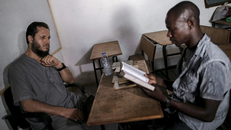 In this photo taken Saturday, March.18, 2017, Abdul Ghani Bandenjki, left, teaches Arabic and the Quran, in a School in Tema, Ghana. Bandenjki first visited Ghana in 2006 after being invited to officiate at prayers during the Ramadan holy month. When fighting broke out in Syria five years later, Bandenjki decided to return to this West African nation more than 3,000 miles (4,825 kilometers) away. (AP Photo/ Jordi Perdigo)