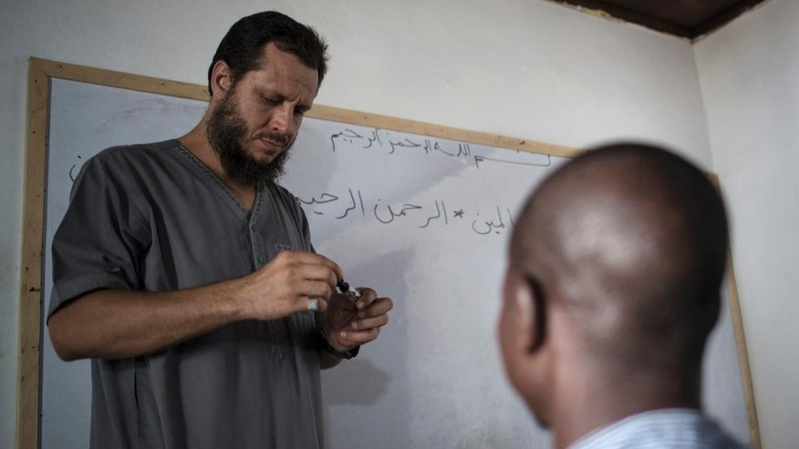 In this photo taken Saturday, March.18, 2017, Abdul Ghani Bandenjki, teaches Arabic and the Quran, in a school in Tema, Ghana. Bandenjki first visited Ghana in 2006 after being invited to officiate at prayers during the Ramadan holy month. When fighting broke out in Syria five years later, Bandenjki decided to return to this West African nation more than 3,000 miles (4,825 kilometers) away. (AP Photo/ Jordi Perdigo)